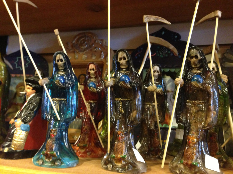 in this Feb. 13, 2013 photo, statues of La Santa Muerte are shown at the Masks y Mas art store in Albuquerque, N.M. La Santa Muerte, an underworld saint most recently associated with the violent drug trade in Mexico, now is spreading throughout the U.S. among a new group of followers ranging from immigrant small business owners to artists and gay activists. In addition to showing up at drug crime scenes, the once-underground icon has been spotted on passion candles in Richmond, Va. grocery stores. The folk saint's image can be seen inside New York City apartments, in Minneapolis religious shops and during art shows in Tucson, Ariz.  (AP Photo/Russell Contreras)