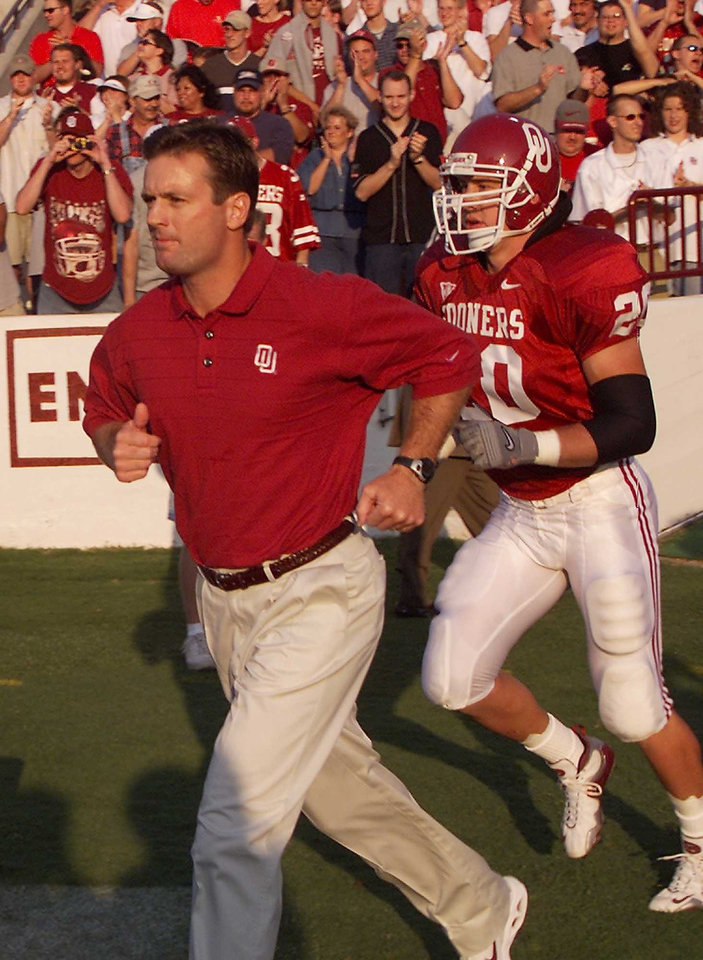 Photo - OU vs Indiana State football. Coach Bob Stoops enters the field with his players. Behind him is Rocky Calmus.