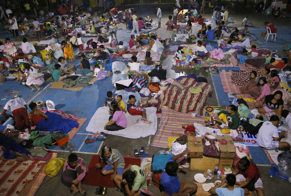 Photo - Typhoon evacuees are housed at a school gymnasium after fleeing their homes due to flooding brought about by Typhoon Koppu in Cabanatuan city in northern Philippines Monday, Oct. 19, 2015. The slow-moving typhoon  blew ashore with fierce wind in the northeastern Philippines early Sunday, toppling trees and knocking out power and communications and forcing the evacuation of thousands of villagers. (AP Photo/Bullit Marquez)