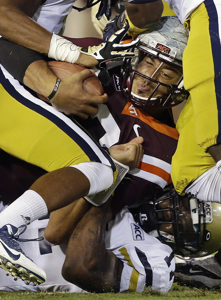 Photo - Virginia Tech quarterback Logan Thomas is stopped by the Georgia Tech defense after a short gain in the first half of an NCAA college football game on Thursday, Sept. 26, 2013, in Atlanta. (AP Photo/John Bazemore)