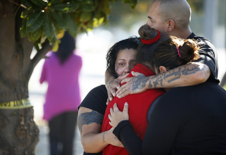 Photo -   Three women and a man, who did not speak to the media, hug together outside the police perimeter in central Fresno where a shooting occurred at a workplace Tuesday, Nov. 6, 2012. A parolee who worked at a California chicken processing plant opened fire at the business on Tuesday, killing one person and wounding three others, before shooting himself, police said. (AP Photo/The Fresno Bee, Craig Kohlruss) LOCAL PRINT OUT; LOCAL TV OUT