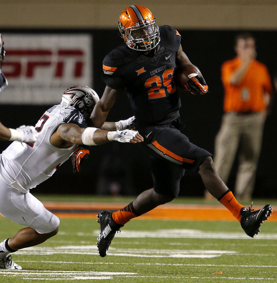 Photo - Oklahoma State's Desmond Roland (26) tries to get past Texas Tech's V.J. Fehoko (52) during a college football game between the Oklahoma State Cowboys (OSU) and the Texas Tech Red Raiders at Boone Pickens Stadium in Stillwater, Okla., Thursday, Sept. 25, 2014. Photo by Bryan Terry, The Oklahoman