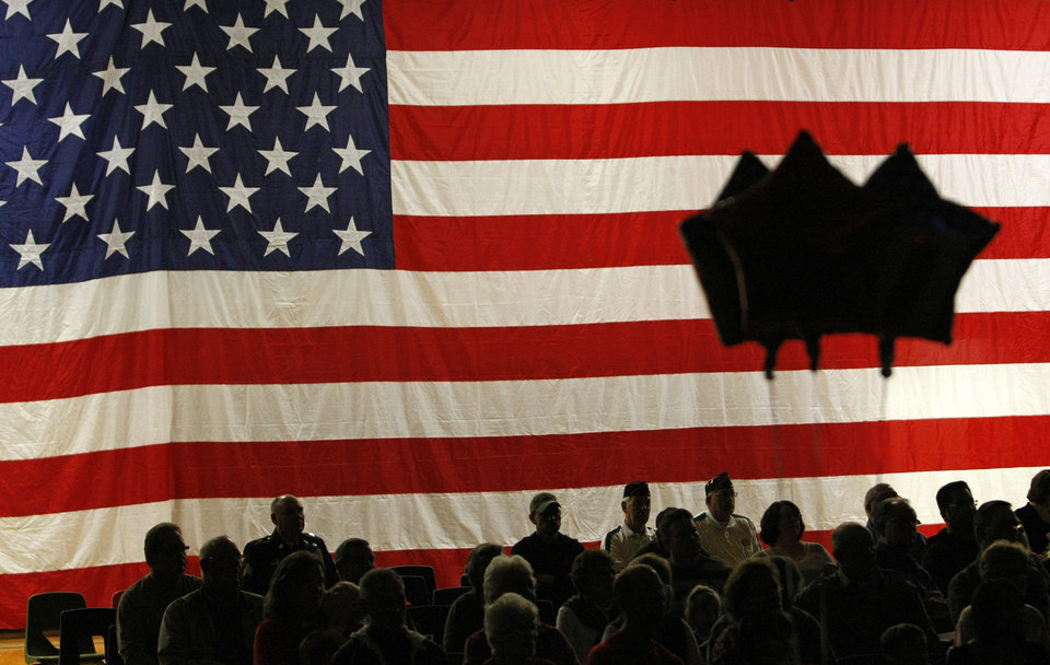 Veterans and their families are silhouetted as they watch a Veterans Day program at Southwestern High School in Hazel Green, Wis., Friday Nov. 9, 2012. (AP Photo/Telegraph Herald, Jeremy Portje)