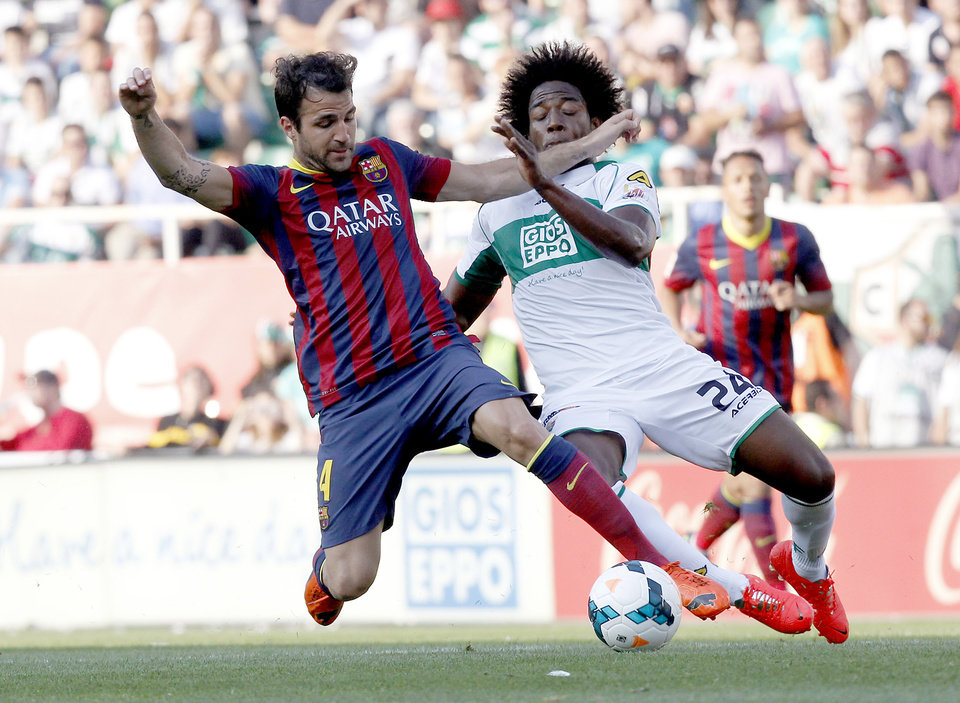 Photo - Barcelona's Cesc Fabregas, left,  duels the ball with Carlos Alberto Sanchez Moreno during a Spanish La Liga soccer match at the Martinez Valero stadium in Elche, Spain, on Sunday, May 11, 2014. (AP Photo/Alberto Saiz)