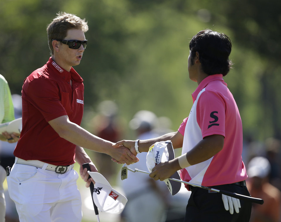 Photo - Chris Stroud, left, shakes hands with Hideki Matsuyama, of Japan, following the second round of the Memorial golf tournament on Friday, May 30, 2014, in Dublin, Ohio. (AP Photo/Darron Cummings)