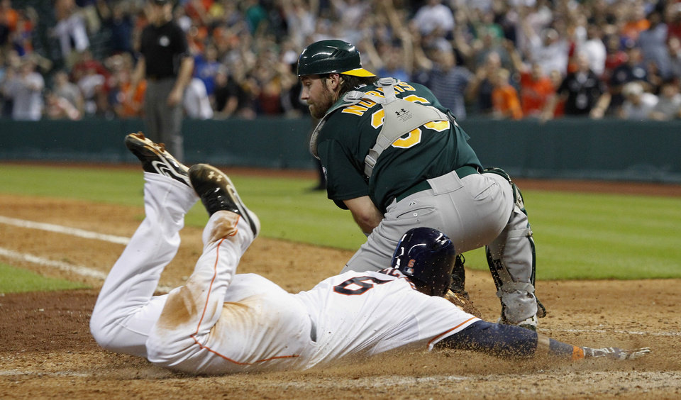 Photo - Houston Astros' Jonathan Villar (6) slides safely at home ahead of Oakland Athletics catcher Derek Norris (36) for the winning run in the ninth inning during a baseball game on Tuesday, July 23, 2013, in Houston. (AP Photo/Bob Levey)