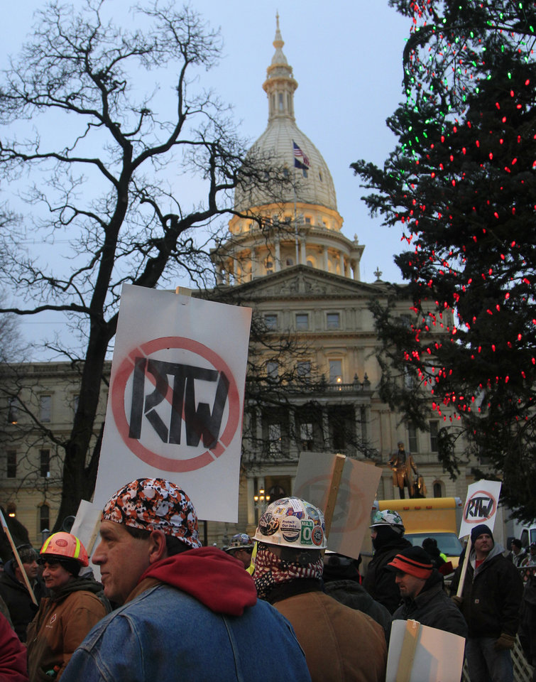 People begin gathering outside on the State Capitol grounds in Lansing, Mich., Tuesday, Dec. 11, 2012 to protest right-to-work legislation that was passed by the state legislature last week.   Michigan will become the 24th right-to-work state, banning requirements that nonunion employees pay unions for negotiating contracts and other services.  (AP Photo/Carlos Osorio)