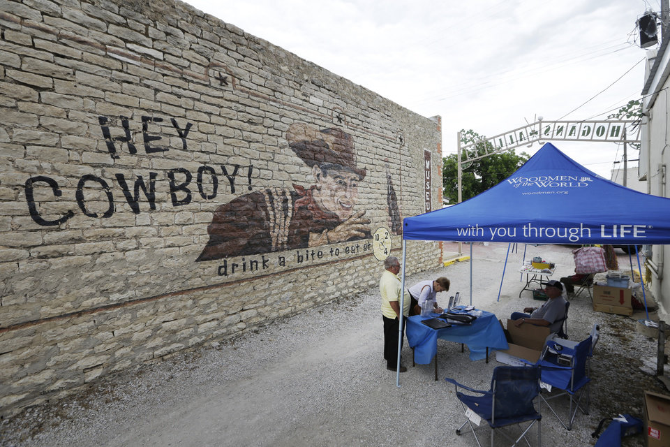Photo - In this June 14, 2014 photo, an alley hosts vendors during a fair in Dublin, Texas. More than two years after Dr Pepper cut ties with the local bottler over a licensing dispute, the town is trying to stabilize its economy by promoting its lesser-known claims to fame, from a festival highlighting its debatable Irish roots, to Dublin's bygone rodeo glories, to its location within the county Dairy Capital of Texas.   (AP Photo/LM Otero)