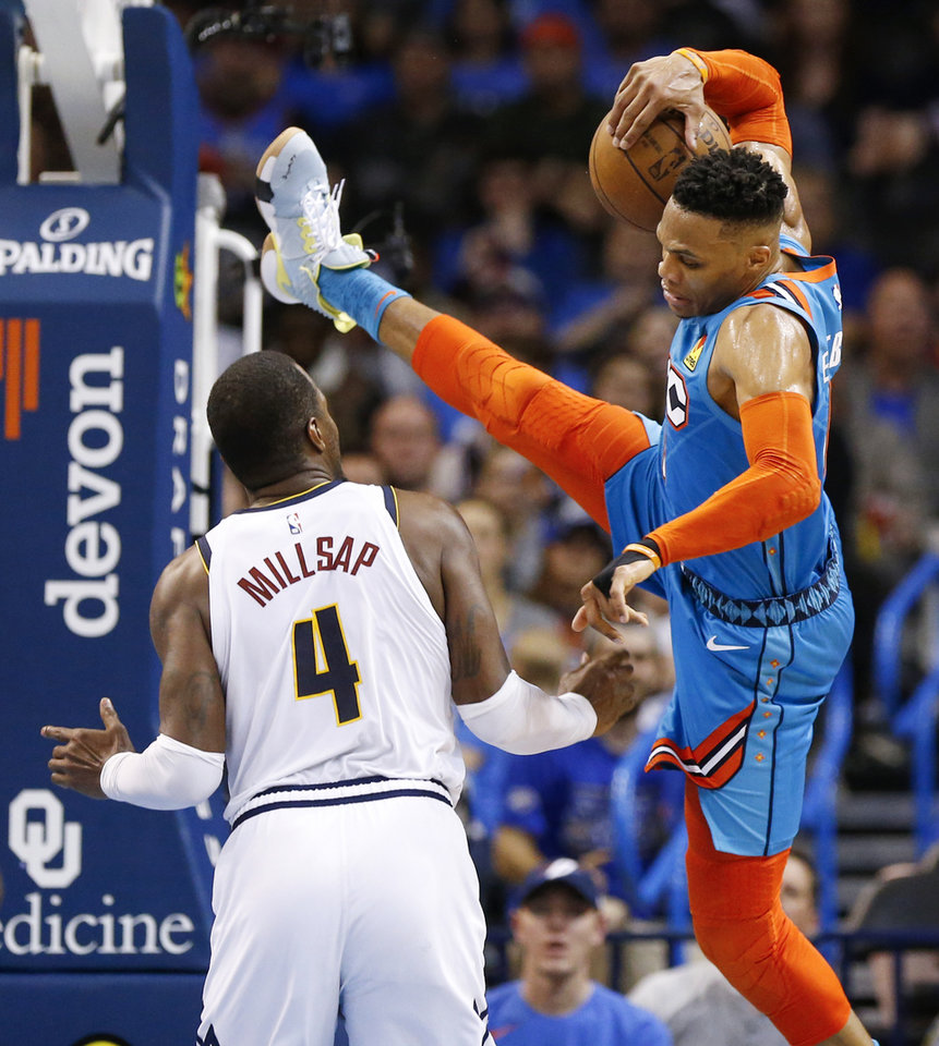 Photo - Oklahoma City's Russell Westbrook (0) falls to the court after being fouled by Denver's Paul Millsap (4) in the fourth quarter during an NBA basketball game between the Denver Nuggets and the Oklahoma City Thunder at Chesapeake Energy Arena in Oklahoma City, Friday, March 29, 2019. Denver won 115-105. Photo by Nate Billings, The Oklahoman