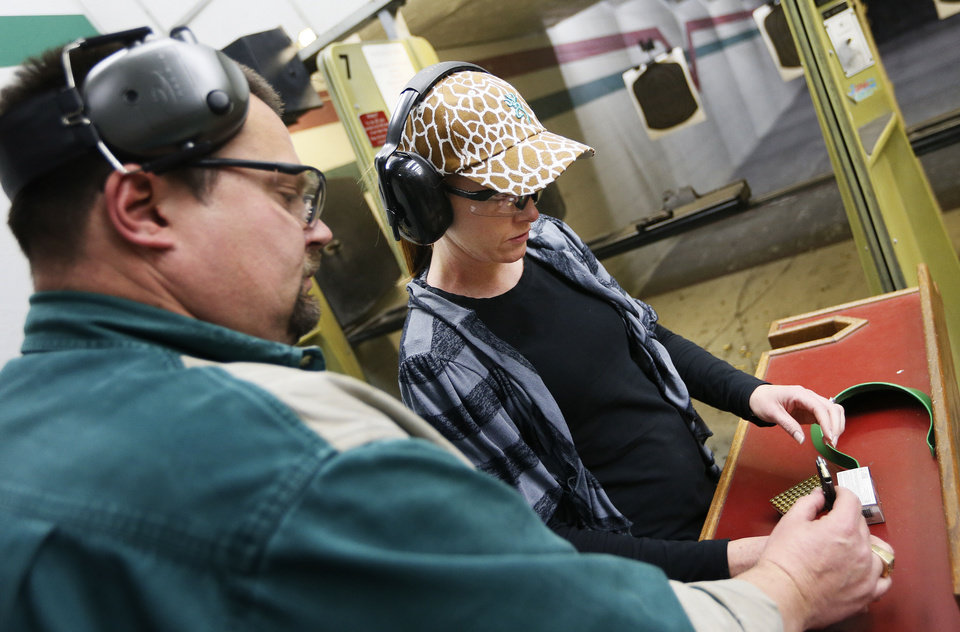 Will Andrews, training coordinator at H&H, shows Tracy Lewis how to load a magazine for her handgun Wednesday during a concealed-carry class at H&H Gun Range and Shooting Sports Complex in Oklahoma City. Photo by Nate Billings, The Oklahoman <strong>NATE BILLINGS</strong>