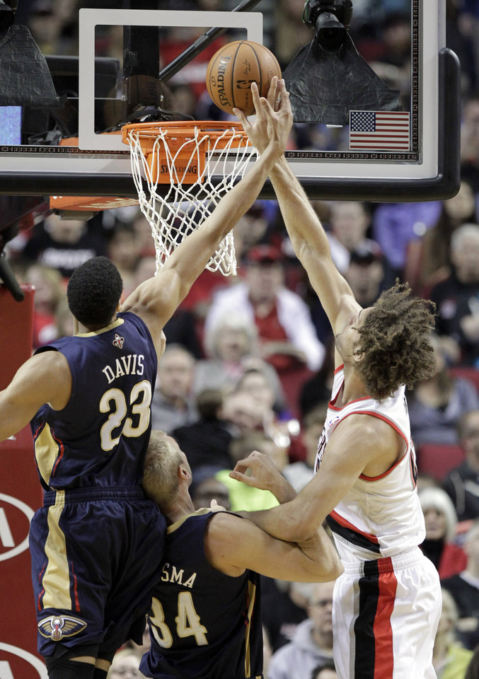 Photo - Portland Trail Blazers center Robin Lopez, right, vies for a rebound with New Orleans Pelicans' Anthony Davis, left, and Greg Stiemsma during the first half of an NBA basketball game in Portland, Ore., Sunday, April 6, 2014. (AP Photo/Don Ryan)
