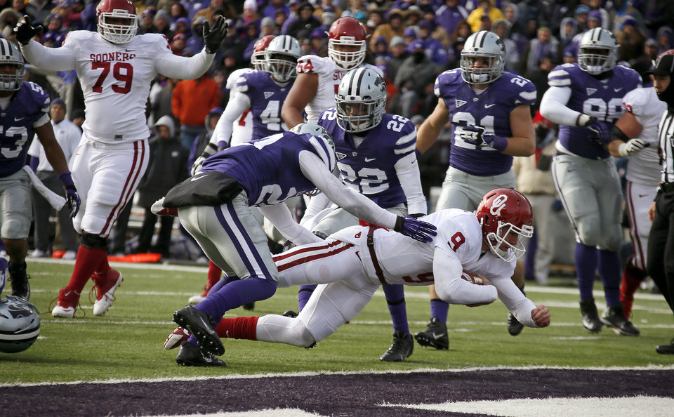 Oklahoma\'s Trevor Knight (9) leaps for a touchdown between Kansas State \'s Dylan Schellenberg (20) and Kansas State \'s Dante Barnett (22) during an NCAA college football game between the Oklahoma Sooners and the Kansas State University Wildcats at Bill Snyder Family Stadium in Manhattan, Kan., Saturday, Nov. 23, 2013. Photo by Bryan Terry, The Oklahoman