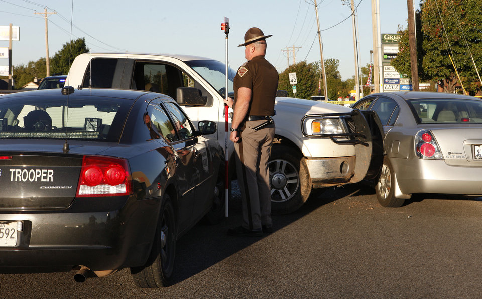 Photo - An Oklahoma Highway Patrol trooper investigates a crash that followed a high-speed chase. The trooper was headed to a fatal tractor-trailer crash in Del City.