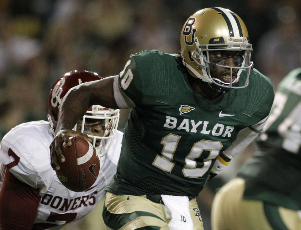 Photo - Baylor quarterback Robert Griffin III (10) is chased out of the pocket by Oklahoma linebacker Corey Nelson (7) in the first half of an NCAA college football game on Saturday, Nov. 19, 2011, in Waco, Texas. (AP Photo/Tony Gutierrez)