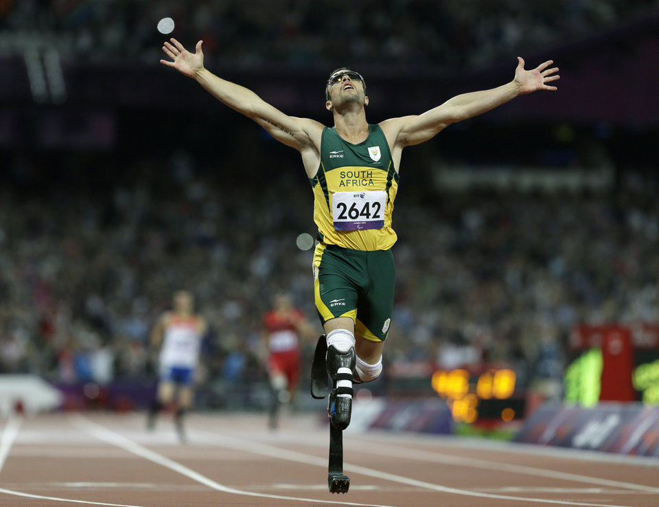 Photo - FILE - In this Sept. 8, 2012 file photo, South Africa's Oscar Pistorius wins gold in the men's 400-meter T44 final at the 2012 Paralympics in London. A judge in South Africa says Pistorius, who is charged with murdering his girlfriend, can leave South Africa to compete in international competition, with conditions. (AP Photo/Kirsty Wigglesworth, File)