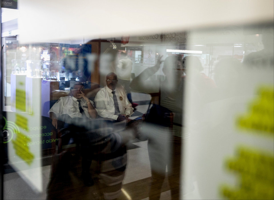 Photo - Security guards sit inside a closed United Airlines office as customers waiting outside for information about ticket sales are reflected in the window in Caracas, Venezuela, Friday, Jan. 24, 2014. Delta, American Airlines and Panama's Copa Airlines were also among carriers whose offices were either closed or had halted sales on Friday after the government devalued the local currency for flights abroad. (AP Photo/Alejandro Cegarra)