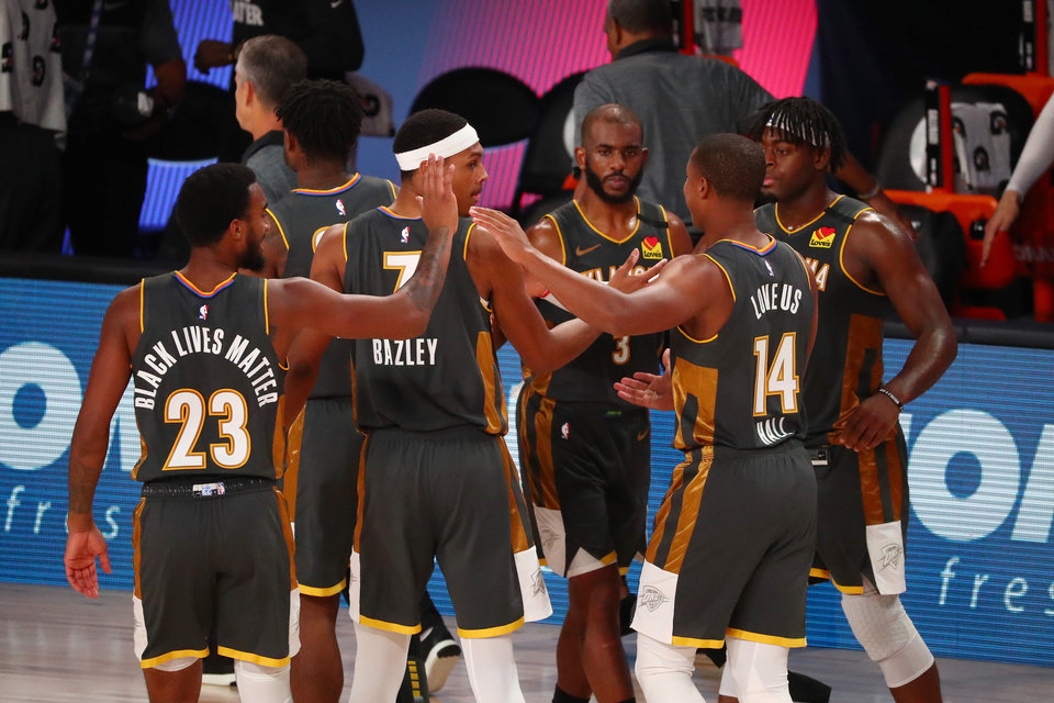 Photo - Aug 9, 2020; Lake Buena Vista, Florida, USA;  Oklahoma City Thunder forward Terrance Ferguson (23) and forward Darius Bazley (7) and guard Chris Paul (3) and guard Devon Hall (14) and guard Luguentz Dort (5) celebrate after defeating the Washington Wizards in a NBA basketball game at AdventHealth Arena. Mandatory Credit: Kim Klement-USA TODAY Sports