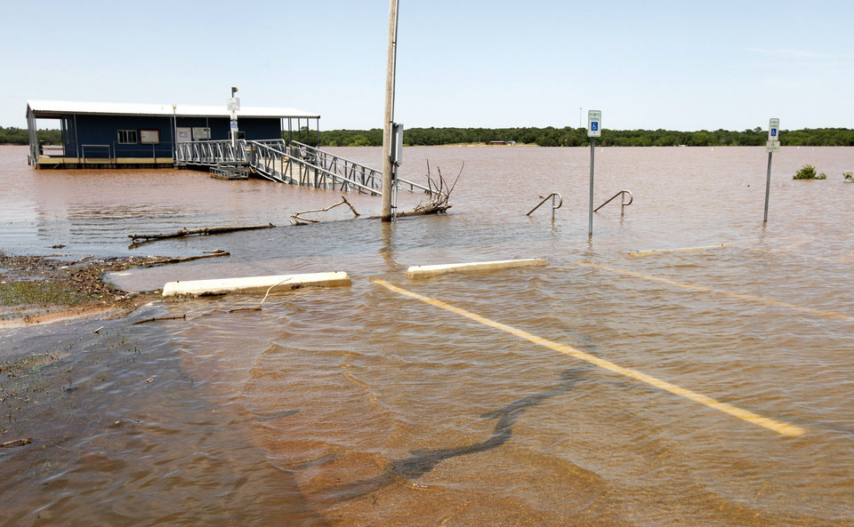 Photo - The parking lot and walkway to the fishing dock at Spring Creek Park at Arcadia Lake were covered by water after the lake flooded following Friday night's storms. PHOTO BY PAUL HELLSTERN, THE OKLAHOMAN.  PAUL HELLSTERN - THE OKLAHOMAN