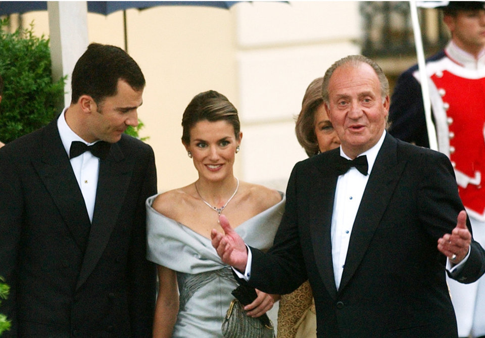 Photo - FILE - In this May 21, 2004 file photo, Spain's Princess Letizia and Prince Felipe, seen a day before their wedding day with King Juan Carlos, right, in Madrid. Spanish Prime Minister Mariano Rajoy says King Juan Carlos plans to abdicate and pave the way for his son, Crown Prince Felipe, to become the country's next king. The 76-year-old Juan Carlos oversaw his country's transition from dictatorship to democracy but has had repeated health problems in recent years. His popularity also dipped following royal scandals, including an elephant-shooting trip he took in the middle of Spain's financial crisis that tarnished the monarch's image. The king came to power in 1975, two days after the death of longtime dictator Francisco Franco.  (AP Photo/Paul White, File)