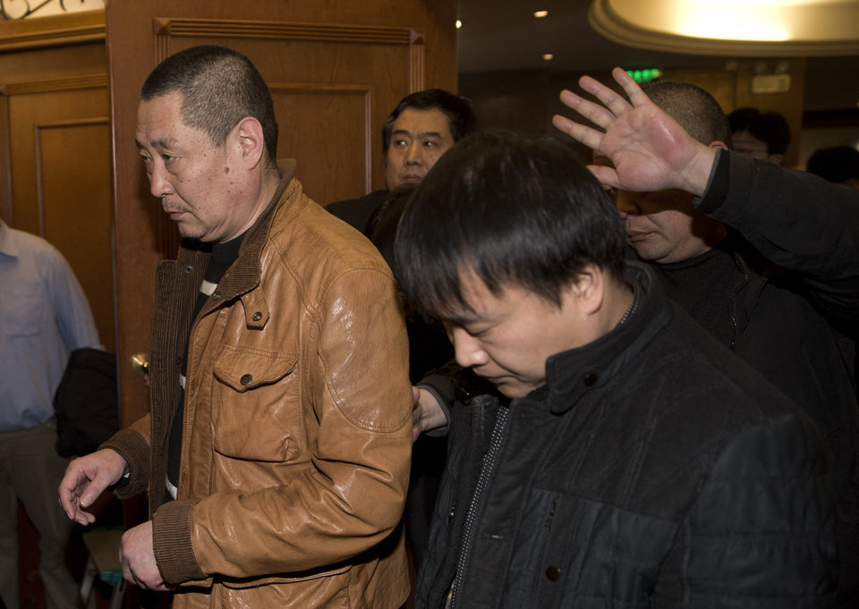 Photo - Chinese relatives of passengers aboard a missing Malaysia Airlines plane walk out from a hotel room after meeting with Malaysian officials, in Beijing, China Wednesday, March 12, 2014. The missing Malaysian jetliner may have attempted to turn back before it vanished from radar, but there is no evidence it reached the Strait of Malacca, Malaysia's air force chief said Wednesday, denying reported remarks he said otherwise. The statement suggested continued confusion over where the Boeing 777 might have ended up, more than four days after it disappeared en route to Beijing from Kuala Lumpur with 239 people on board. (AP Photo/Andy Wong)