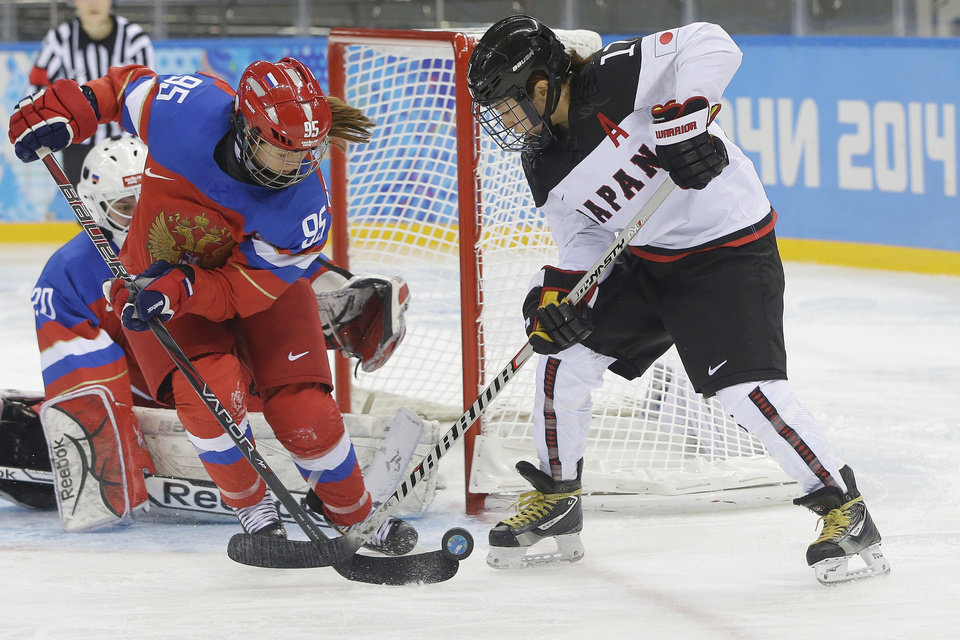Photo - Yelena Dergachyova of Russia and Yuka Hirano of Japan battle for control of the puck during the 2014 Winter Olympics women's ice hockey game at Shayba Arena Sunday, Feb. 16, 2014, in Sochi, Russia. (AP Photo/Matt Slocum)