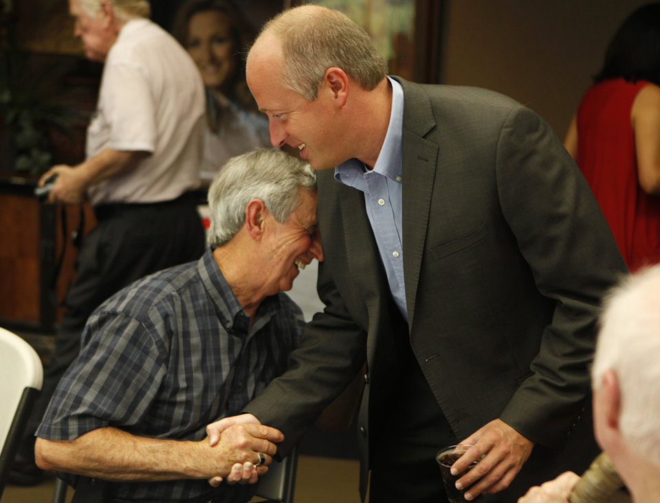 Photo - Brian Maughan (right), greets Ray Reaves, of Oklahoma City, during a watch party for Brian Maughan, incumbent candidate for county commissioner, Tuesday, June 26, 2012.  Photo by Garett Fisbeck, The Oklahoman