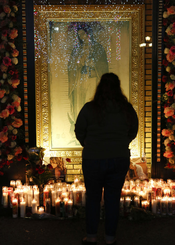 Fan Jenny Guerrero pays tribute to singer Jenni Rivera at a makeshift memorial in front of an image of the Virgin of Guadalupe at the Plaza Mexico shopping center in Lynwood, Calif., early Monday, Dec. 10, 2012. Authorities have not confirmed her death, but Rivera's relatives in the U.S. say they have few doubts that she was on the Learjet 25 that disintegrated on impact Sunday in rugged territory in Nuevo Leon state in northern Mexico. (AP Photo/Patrick T. Fallon)