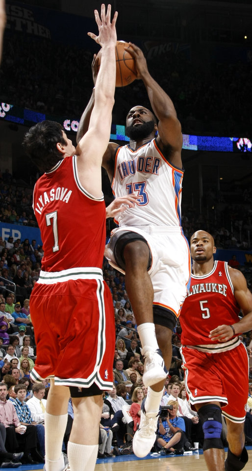 Photo - Oklahoma City's James Harden (13) goes between Milwaukee's Ersan Ilyasova (7) and Milwaukee's Corey Maggette (5) during the NBA basketball game between the Oklahoma City Thunder and the Milwaukee Bucks at the Oklahoma City Arena, Wednesday, April 13, 2011. Photo by Bryan Terry, The Oklahoman