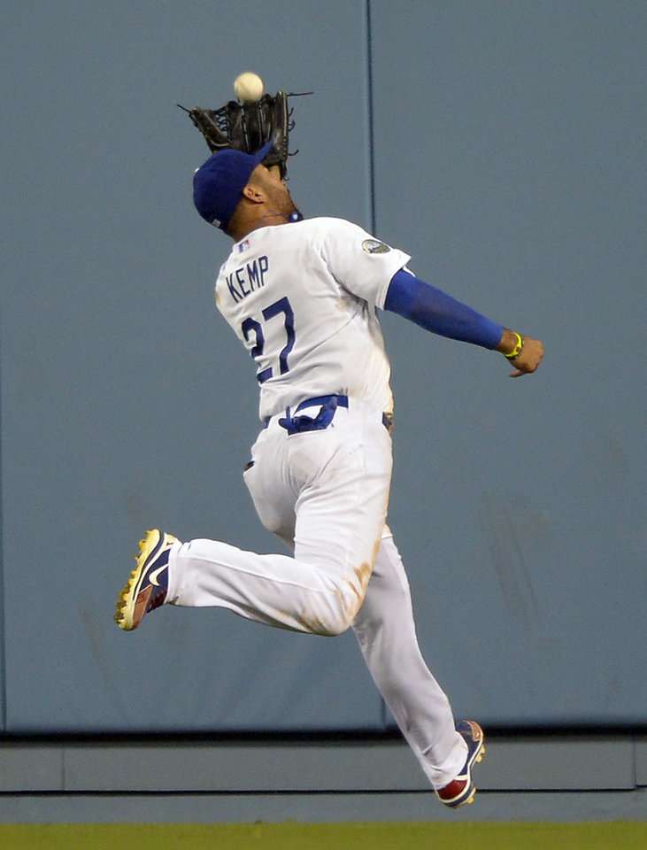 Photo -   Los Angeles Dodgers center fielder Matt Kemp makes a catch over his head on a ball hit by St. Louis Cardinals' Daniel Descalso during the eighth inning of their baseball game, Thursday, Sept. 13, 2012, in Los Angeles. (AP Photo/Mark J. Terrill)