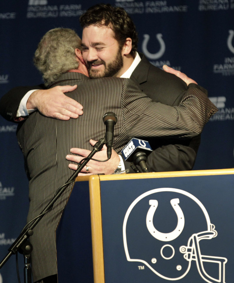 Photo - Jeff Saturday, right, gets a hug from Colts owner Jim Irsay  at a news conference before signing a one day contract in order to retire as an Indianapolis Colt Thursday, March 7, 2013, in Indianapolis. Saturday spent 13 seasons in Indianapolis before signing with Green Bay last year. (AP Photo/AJ Mast)