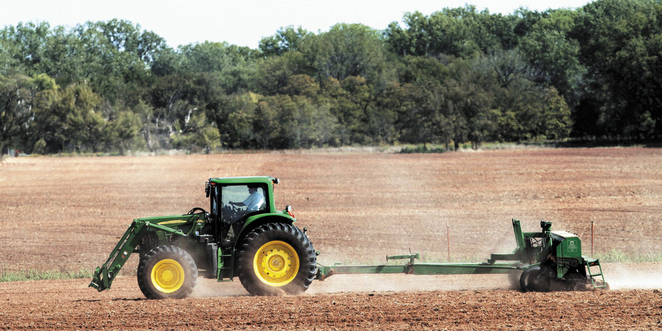 Photo - David Harman, of El Reno, plants wheat in one of his fields in Canadian County. Photo by Jim Beckel, The Oklahoman