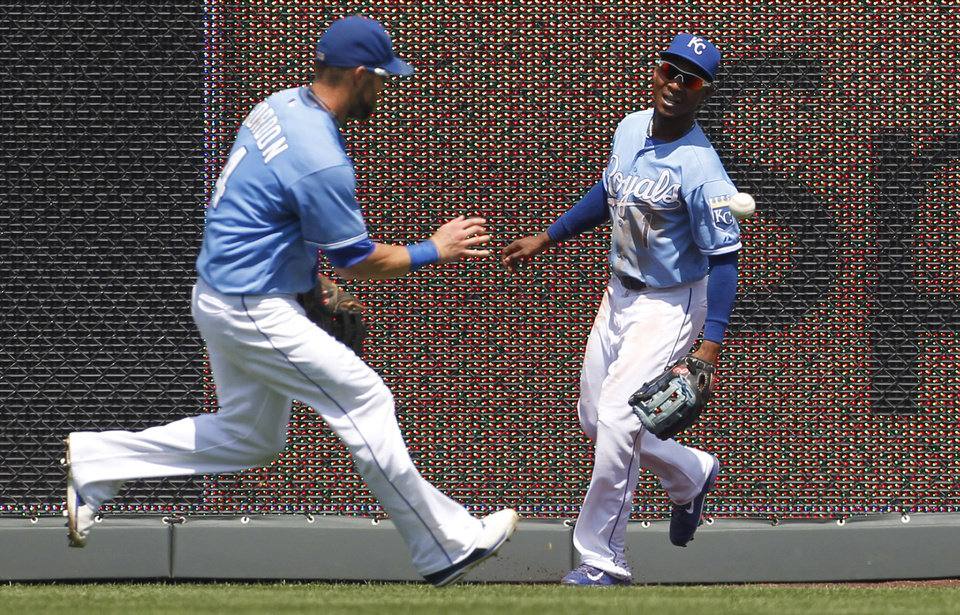 Photo - Kansas City Royals left fielder Alex Gordon (4) and center fielder Jarrod Dyson go after a ball hit by Washington Nationals' Anthony Rendon that bounced off the wall in the third inning of a baseball game at Kauffman Stadium in Kansas City, Mo., Sunday, Aug. 25, 2013. Rendon doubled on the play. (AP Photo/Colin E. Braley)