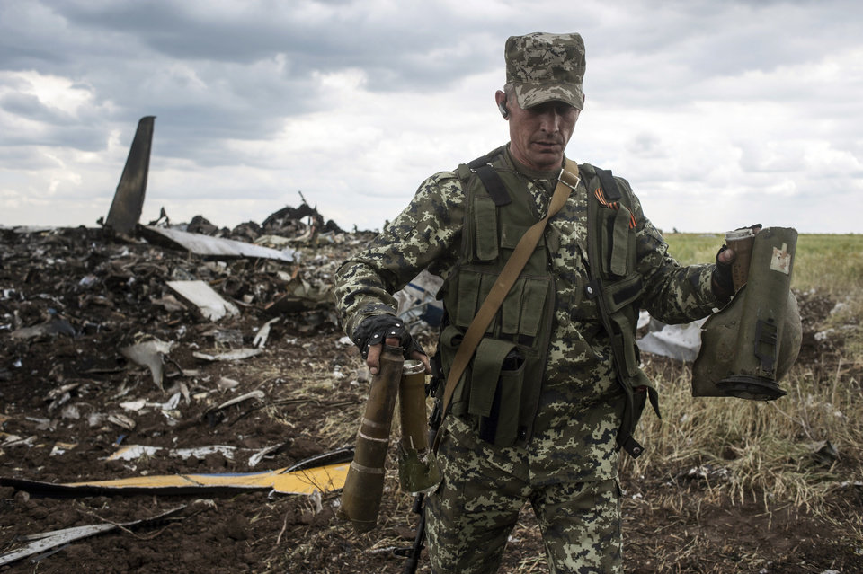 Photo - A pro-Russian fighter carries parts of weapons from the site of remnants of a downed Ukrainian army aircraft Il-76 at the airport near Luhansk, Ukraine, Saturday, June 14, 2014. Pro-Russian separatists shot down the military transport plane Saturday in the country's restive east, killing all 49 service personnel on board, Ukrainian officials said. (AP Photo/Evgeniy Maloletka)