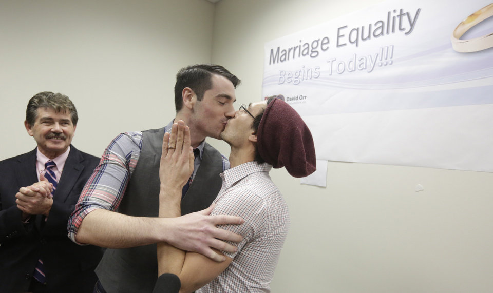 Photo - CORRECTS SPELLING TO WILK IN SECOND REFERENCE INSTEAD OF WILL - Charlie Gurion, center, and David Wilk kiss after obtaining their marriage license as Cook County Clerk David Orr, left,looks on Friday, Feb. 21, 2014, in Chicago. Same-sex couples in Illinois' largest county began receiving marriage licenses immediately after a federal judge's ruling Friday that some attorneys said could give county clerks statewide justification to also issue the documents right away. Illinois approved same-sex marriage last year; the new law takes effect June 1. However, U.S. District Judge Sharon Johnson Coleman ruled Friday that same-sex marriages can begin now in Cook County, where Chicago is located. Gurion and Wilk were the first couple to show up to get a license after the judge made her ruling. (AP Photo/M. Spencer Green)