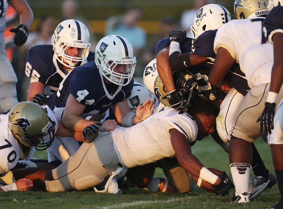 Photo - Heritage Hall's AJ Knowles (15) loses his helmet as he goes down during a game at Casady High School in The Village, Okla., Thursday, Aug. 30, 2012.  Photo by Garett Fisbeck, The Oklahoman