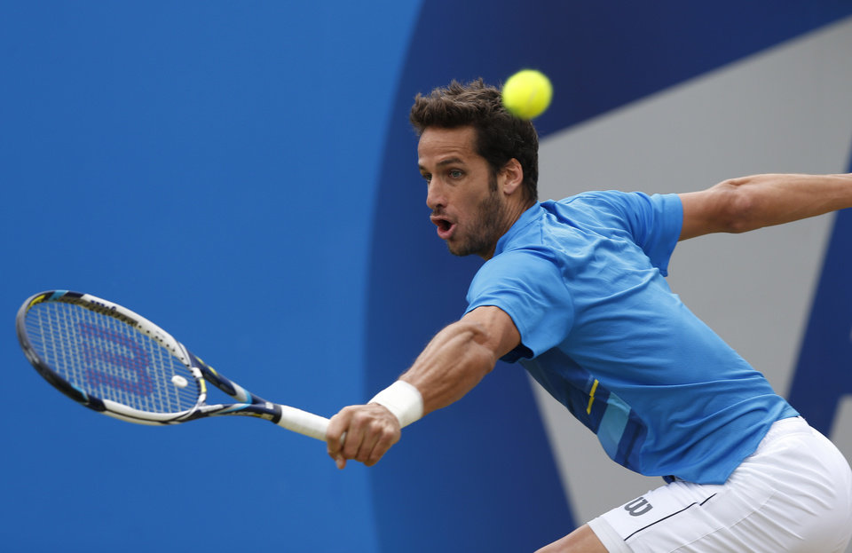 Photo - Feliciano Lopez of Spain plays a return to Grigor Dimitrov of Bulgaria during their Queen's Club grass court championships singles final tennis match in London, Sunday, June 15, 2014. (AP Photo/Sang Tan)