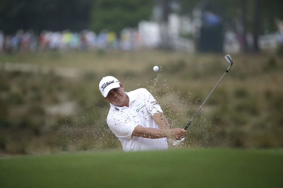 Photo - Jason Dufner hit out of the bunker on the 12th hole during the second round of the U.S. Open golf tournament in Pinehurst, N.C., Friday, June 13, 2014. (AP Photo/David Goldman)