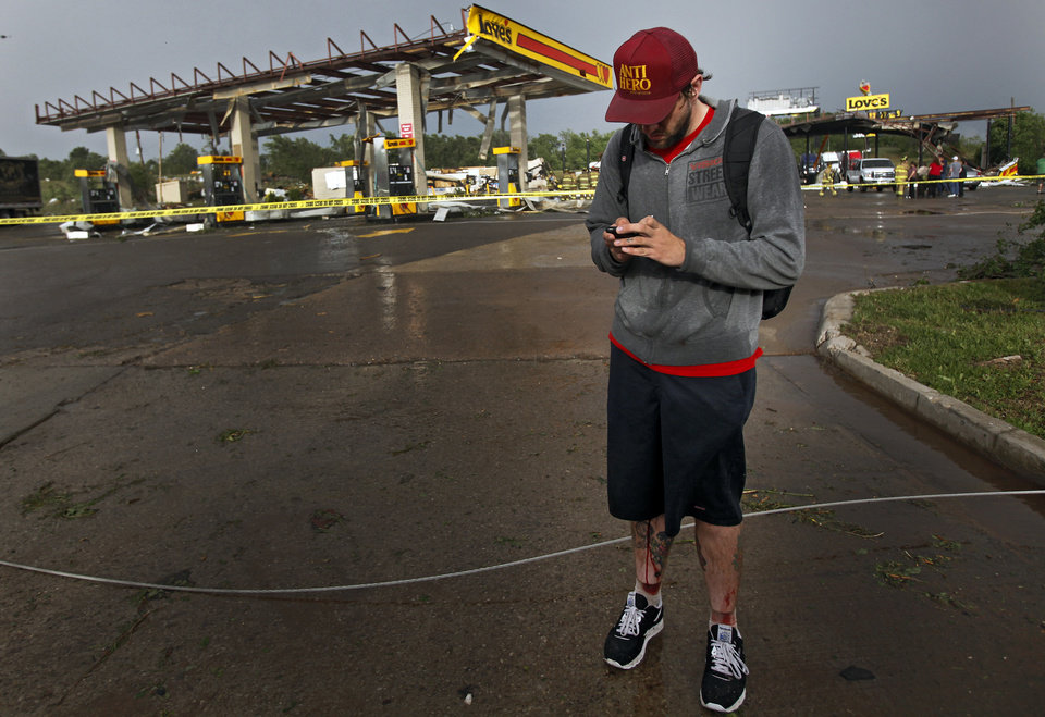 Photo - Jesse Smith has blood running down his leg as he uses his phone after a tornado caused him to crash his car at the Love's Country Store that was destroyed by the tornado at I-40 and Choctaw Road on Monday, May 10, 2010, in Oklahoma City, Okla.  Photo by Chris Landsberger, The Oklahoman