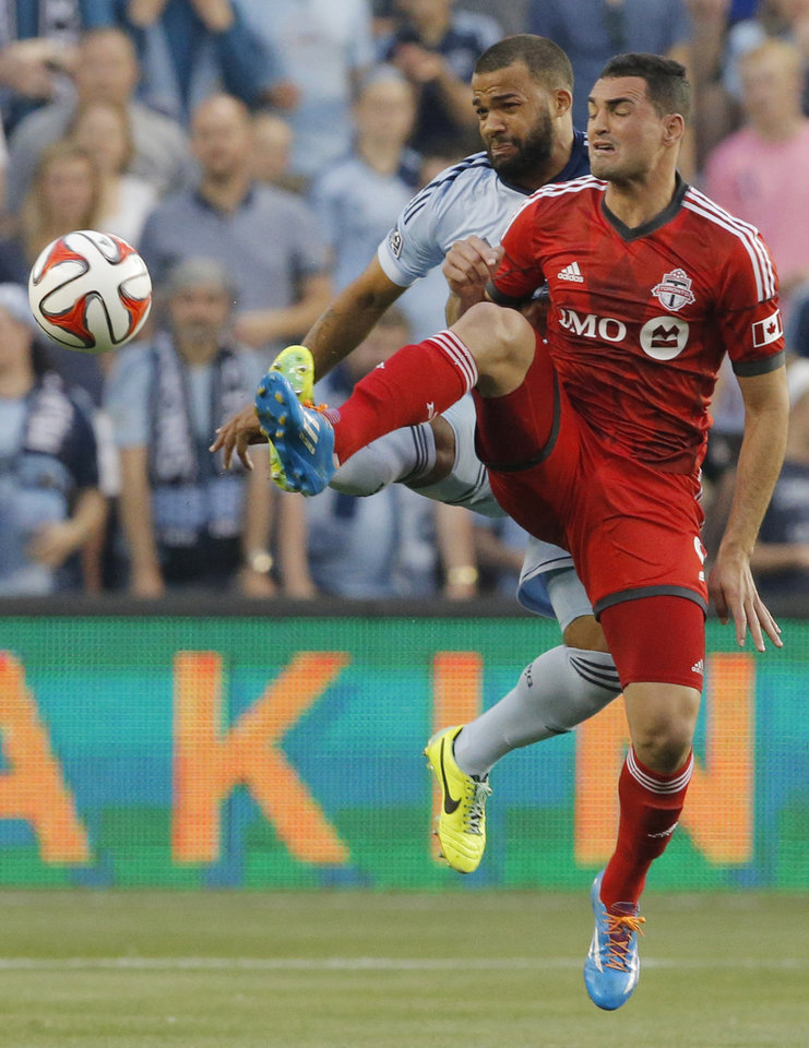 Photo - Toronto FC forward Gilberto, front, and Sporting Kansas City defender Kevin Ellis, back, play the ball during the first half of an MLS soccer match in Kansas City, Kan., Friday, May 23, 2014. (AP Photo/Orlin Wagner)