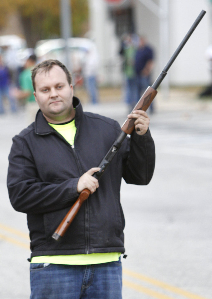 Joseph Hughes fires a shotgun to start the Turkey Trot fun run.
