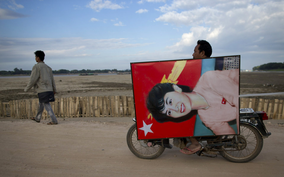 Photo - A supporter of opposition leader Aung San Suu Kyi rides a motor bike transporting a portrait of her for a public rally close to Letpadaung mine in Monywa, northwestern Myanmar, Friday, Nov 30, 2012.  Opposition leader Aung San Suu Kyi has publicly criticized the forcible crackdown on protesters at a mine in northwestern Myanmar, saying the public needs an explanation of the violence that injured dozens, including Buddhist monks.   (AP Photo/Gemunu Amarasinghe)