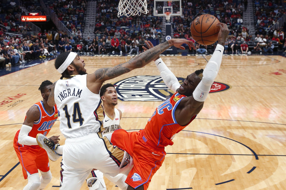 Photo - New Orleans Pelicans forward Brandon Ingram (14) blocks a shot by Oklahoma City Thunder guard Dennis Schroder, right, in the second half of an NBA basketball game in New Orleans, Sunday, Dec. 1, 2019. (AP Photo/Gerald Herbert)