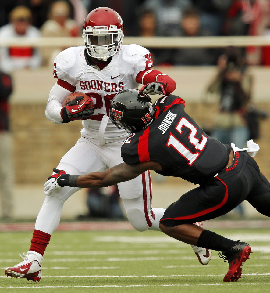Photo - Oklahoma's Damien Williams (26) tries to get past Texas Tech's D.J. Johnson (12) during a college football game between the University of Oklahoma (OU) and Texas Tech University at Jones AT&T Stadium in Lubbock, Texas, Saturday, Oct. 6, 2012. OU won, 41-20. Photo by Nate Billings, The Oklahoman