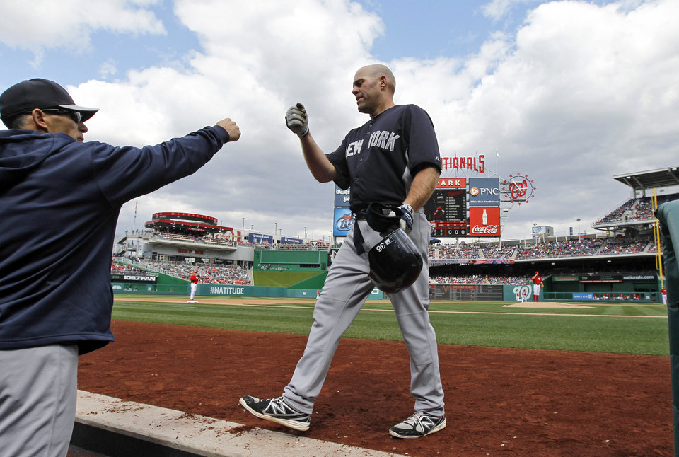 Photo - New York Yankees manager Joe Girardi, left, congratulates Kevin Youkilis after his solo home run during the fourth inning of an exhibition baseball game at Nationals Park on Friday, March 29, 2013, in Washington. (AP Photo/Alex Brandon)