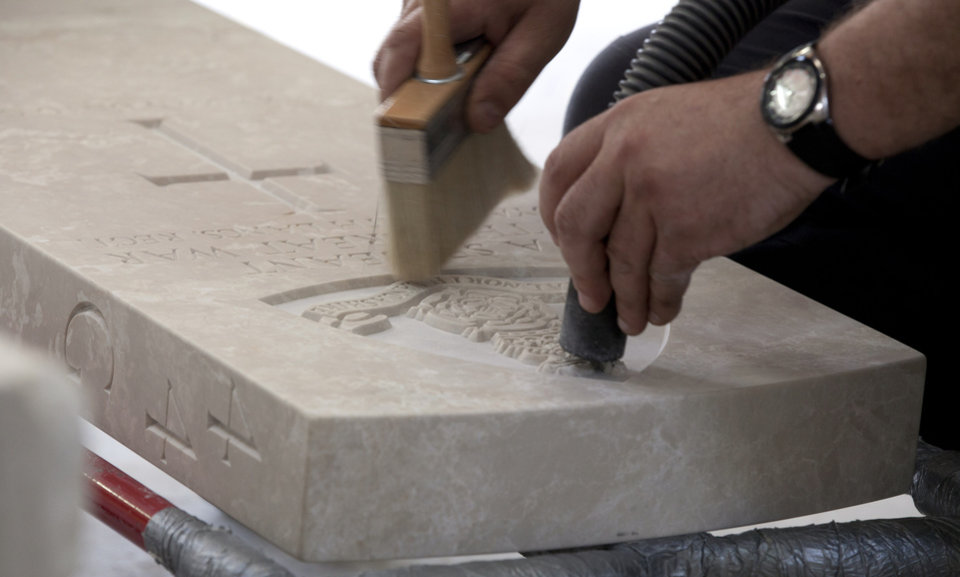 Photo - A worker uses a brush and vacuum to remove excess dust off of the headstone of a WWI soldier after it has been engraved at the workshop of the Commonwealth War Graves Commission in Beaurains, France, on Wednesday, April 17, 2013. Commonwealth cemeteries and monuments around the world are currently being renovated in preparation for centenary events which begin in 2014. (AP Photo/Virginia Mayo)