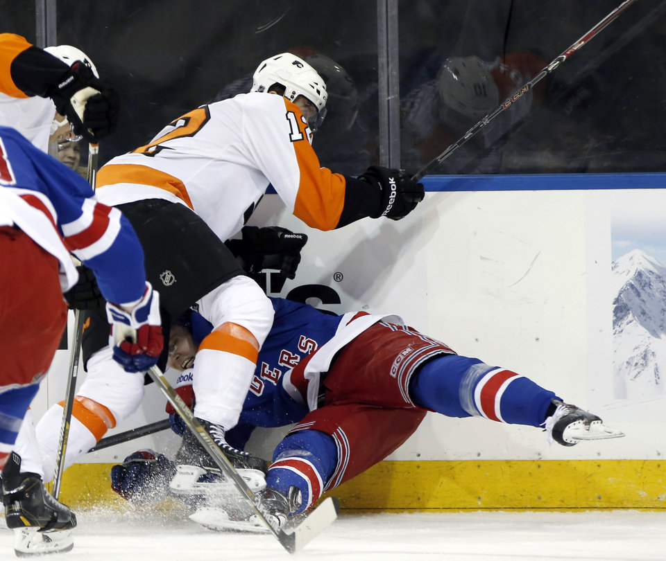 Photo - Philadelphia Flyers left wing Michael Raffl (12) sends New York Rangers defenseman Anton Stralman (6) of Sweden to the ice in the first period of Game 2 of the first round of the Stanley Cup hockey playoffs at Madison Square Garden in New York , Sunday, April 20, 2014.  (AP Photo/Kathy Willens)