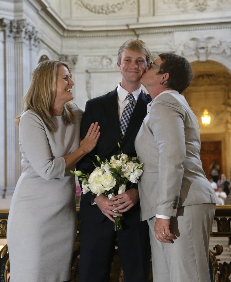 Photo - Elliott Perry, center, is kissed by his mother, Kris Perry, after his parents, Sandy Stier, left, and Perry were wed by California Attorney General Kamala Harris at City Hall in San Francisco, Friday,  June 28, 2013. Stier and Perry, the lead plaintiffs in the U.S. Supreme Court case that overturned California's same-sex marriage ban, tied the knot about an hour after a federal appeals court freed same-sex couples to obtain marriage licenses for the first time in 4 1/2 years.(AP Photo/Marcio Jose Sanchez)