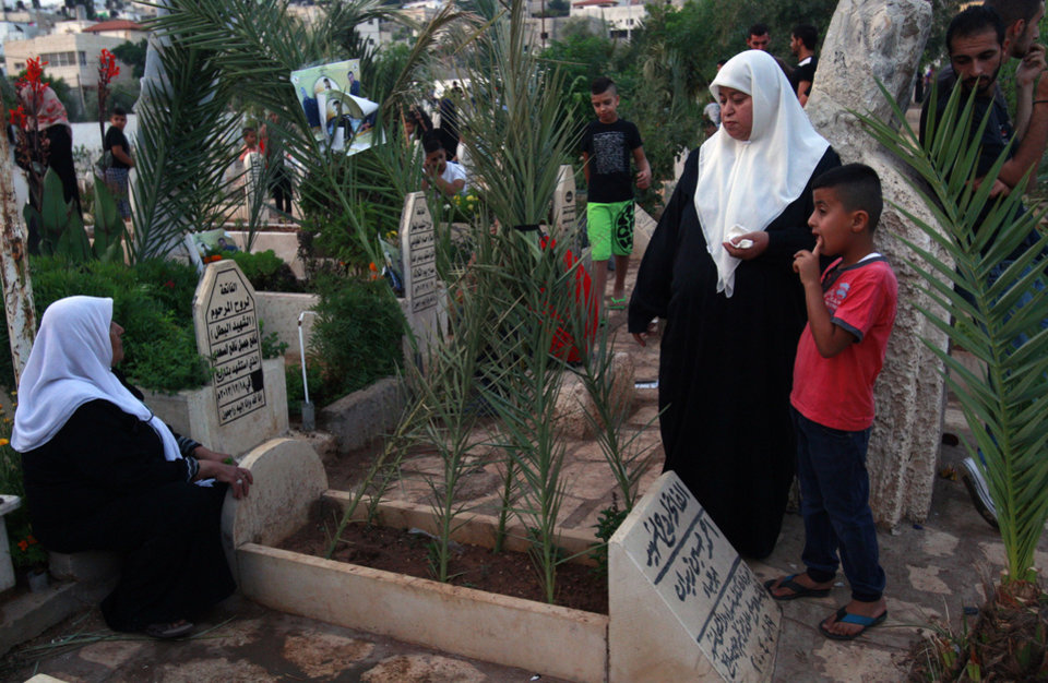Photo - Palestinian Muslims visit the graves of a relatives on the first day of Eid al-Fitr, in the Jenin refugee camp, West Bank, Monday, July 28, 2014. Monday marked the beginning of the three-day Eid holiday, which caps the Muslim fasting month of Ramadan. Muslims usually start the day with dawn prayers and visiting cemeteries to pay their respects to the dead, with children getting new clothes, toys, shoes and haircuts, and families visiting each other. (AP Photo/Mohammed Ballas)