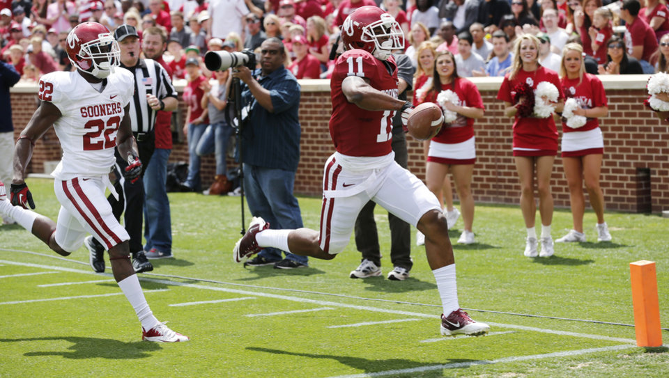 Photo - Lacoltan Bester (11) scores after picking up a fumble by Damien Williams during the annual Spring Football Game at Gaylord Family-Oklahoma Memorial Stadium in Norman, Okla., on Saturday, April 13, 2013. Photo by Steve Sisney, The Oklahoman