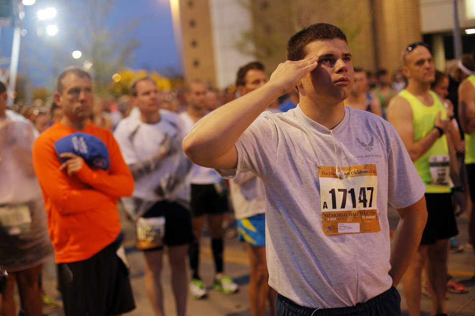 Photo - John Atterson salutes during the national anthem before the Oklahoma City Memorial Marathon in Oklahoma City, Sunday, April 28, 2013.  Photo by Garett Fisbeck, For The Oklahoman